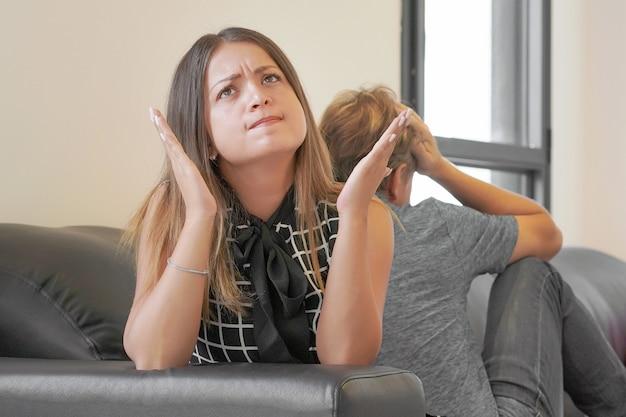 屋内の家のリビングルームのソファに座って引数または別れた後悲しいカップル。
