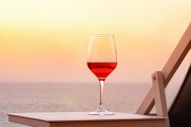 夕日の海を背景に赤ワインのガラス。ロマンチックなデートのコンセプト