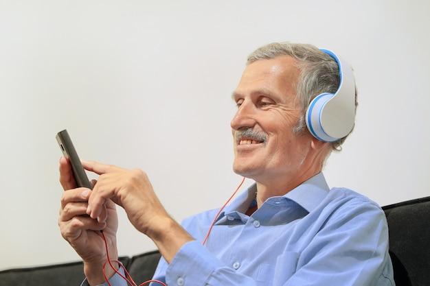 Пожилой мужчина в наушниках слушает музыку