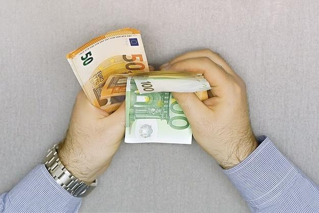手を保持し、ユーロ紙幣を数える
