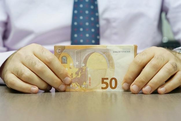 Руки держат и считают банкноты евро