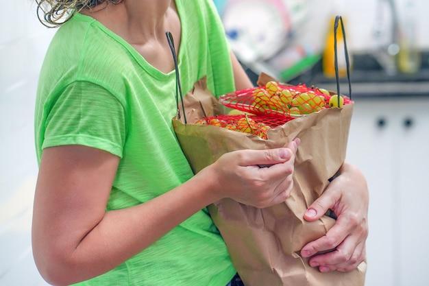 Рука девушки с сумками еды дома.