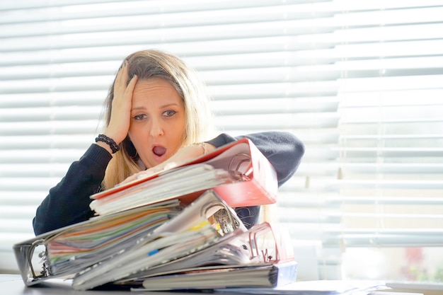 たくさんの書類を持って一人でオフィスで働いています。悪い結果を叫んで叫ぶ