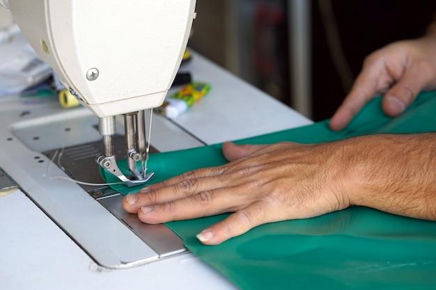 男仕立て屋。革の縫製の背後にある男性の手。