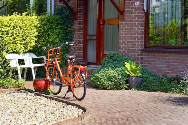 民家の近くのオレンジ色の自転車