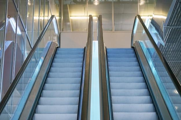空のエスカレーターの階段。ショッピングモールの現代エスカレーター、デパートのエスカレーター。ガラスの建物内の空のエスカレーター。