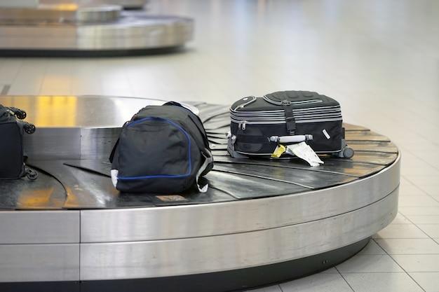 Багаж на конвейерной ленте в аэропорту. зона получения багажа в аэропорту, абстрактная багажная линия с множеством чемоданов.