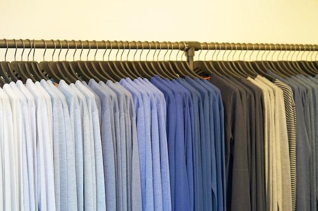 Вешалка для одежды с футболкой. модная одежда на вешалках в магазине. спортивные футболки висят на вешалке для одежды, красочные футболки