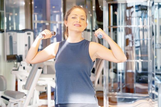 ジムでダンベルの女性運動。ダンベルで働くかわいいフィットネス女の子。