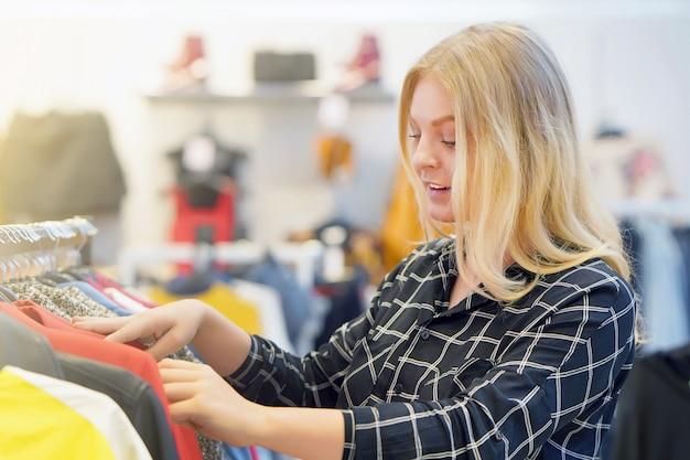 Молодая блондинка, выбирайте новые вещи в магазине. красивая покупательница выбирает понравившиеся вещи в бутике.
