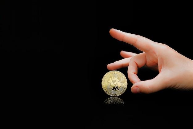 女性の指はビットコインを捨てます。ビットコイン。ビットコインと新しい仮想マネーのコンセプト。ビットコインは新しい通貨です。