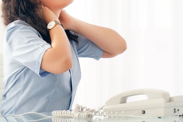 Боль в шее у женщины от усталости. утомленная шея. офисный работник женщина страдает от боли в шее.
