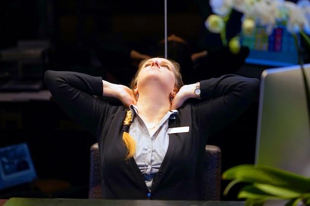 Утомленная шея. менеджер отеля. женщина-приемная страдает от боли в шее.