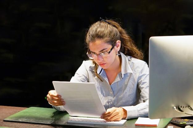オフィスワーカーのクローズアップは、手紙で否定的なニュースを読み取ります。ショックを受けた少女は、会社からの解雇に驚いた。