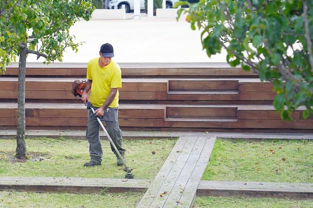 都市公園でエッジトリマーを使用するプロの庭師。晴れた日に屋外で草トリマーと芝生を刈る高齢男性労働者。