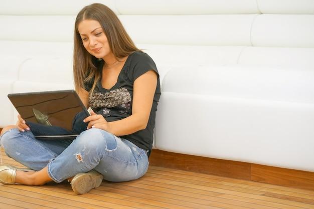 自宅で美しい女性のラップトップで床に座って
