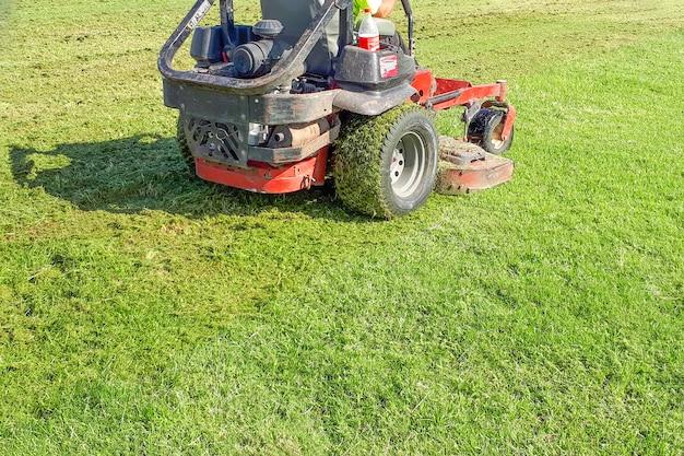 自動芝刈り機。男は芝刈り機に乗る。芝生の手入れ。乗馬芝刈り機。草