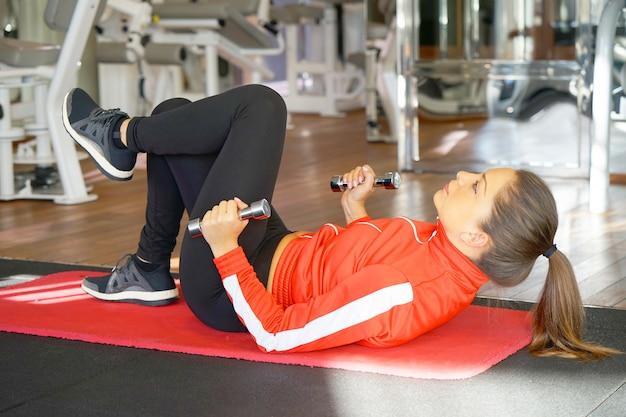 Спортивный женщина делает упражнения с гантелями на полу.