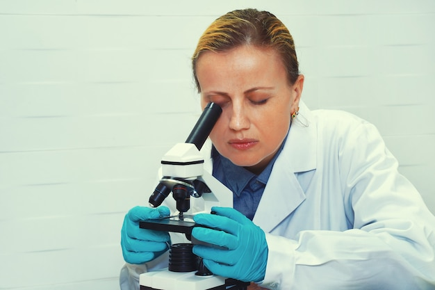 Ученый с пробным стеклом работает в лаборатории. жизнь ученого исследует в лаборатории. женский биохимик смешивает вещества для изучения под микроскопом.