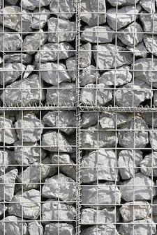 Каменная кладка, под железной проволокой. текстура стены из маленьких серых камней под железной сеткой.