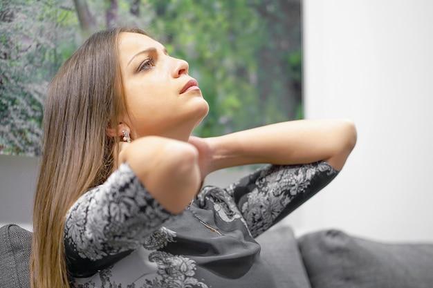 自宅のソファで首の痛みに苦しんでいる女性。女性の疲労感、疲労、ストレス。疲れた首。