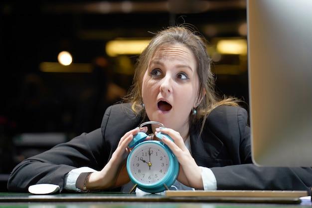時計を保持している女性。女性は職場で彼女の手で目覚まし時計を保持しています。