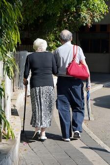 高齢の女性と男性が公園を散歩します。