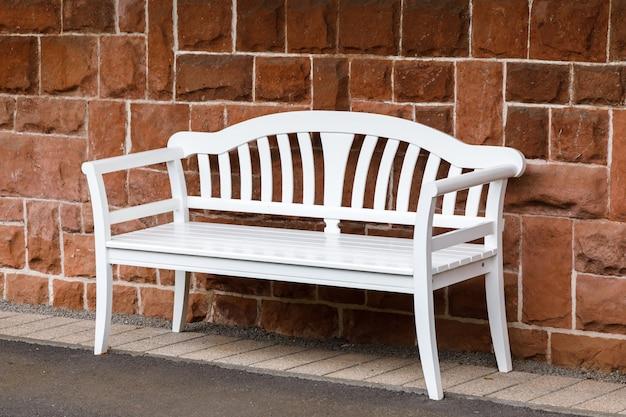 カーリーバックと手すりを備えた単一の白い木製ベンチ
