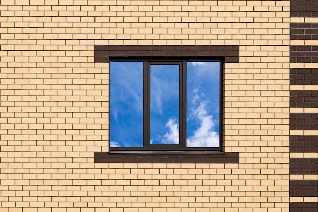 Окно с тремя стеклами против новой кирпичной стены.