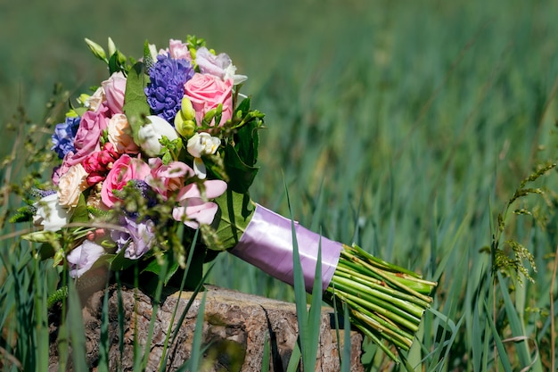 Красивый свадебный букет лежит на пеньке в высокой траве