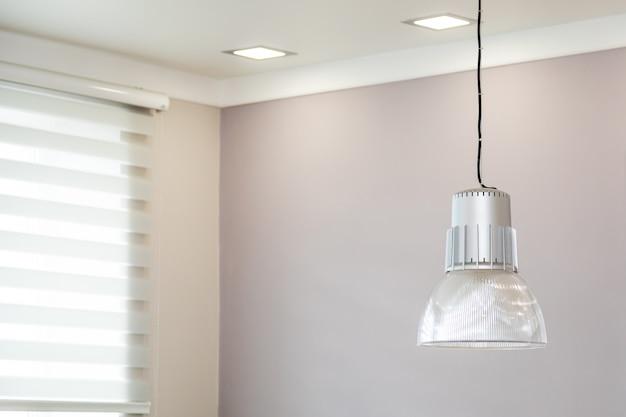 ユニバーサルオフィスの天井の下に大きな天井ランプシェードが付いたモダンなランプ。