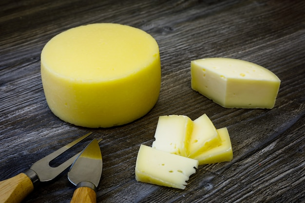 ファームヤギチーズ、フォーク、チーズナイフ木製テーブルの上