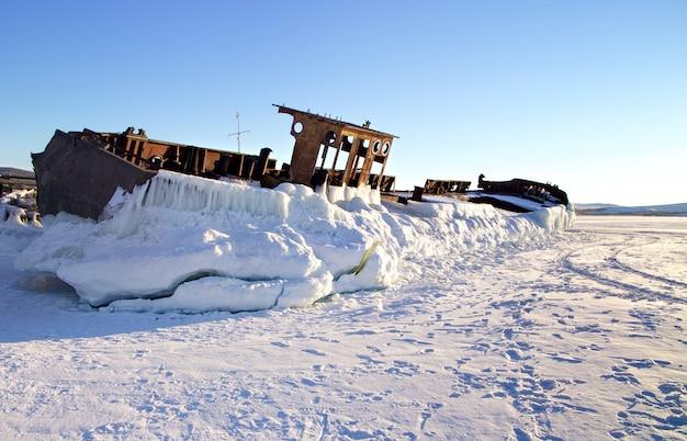 凍った湖の海岸に置かれた放棄された古いさびた船。バイカル、ロシア