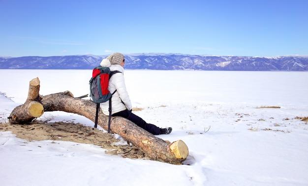 旅行のコンセプト。バイカル湖、シベリア、ロシアのバックパック劇場版ビューを持つ女性ハイカー。冬の観光。