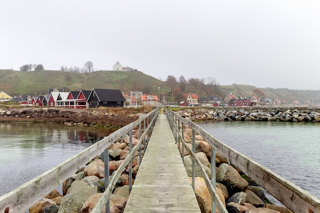フォアグラウンドで桟橋とオーレスンの島ベンのマリーナの家