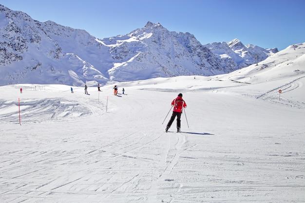 男がスキー場でスキーをしています。冬の山々、パノラマ-イタリアアルプスの雪を頂いたピーク