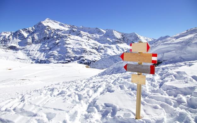 イタリアアルプスのスキーリゾートの方向標識。パスを示す木製看板と冬山のパノラマ。抽象的な概念