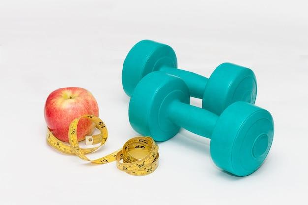 青いダンベル、赤いリンゴ、白い背景の上のテープ