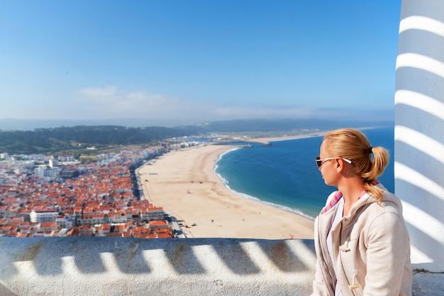 Молодая женщина, сидя на точке зрения и глядя на береговой линии океана в назаре, португалия
