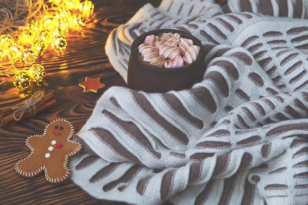 マシュマロ、ジンジャーブレッド、シナモン、古いヴィンテージの木製とクリスマスライトの暖かい毛布で熱いココアの大きなカップ。居心地の良いクリスマスや秋のアレンジメント。