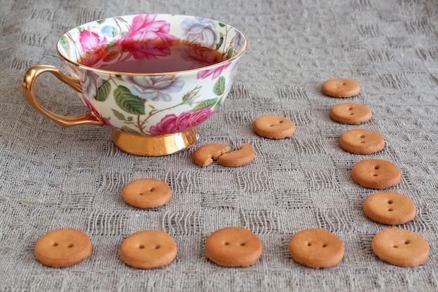 Чашка чая с круглыми крекерами на белье