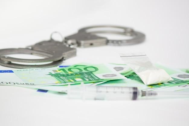 麻薬密売に対する刑罰は刑務所です。ユーロ紙幣、コカイン、白い背景の上の注射器に手錠