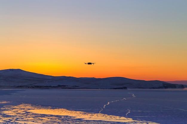 日没で飛んでいるドローンのシルエット