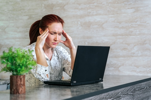 若い女性のストレスとオフィスで座っている頭痛で疲れた