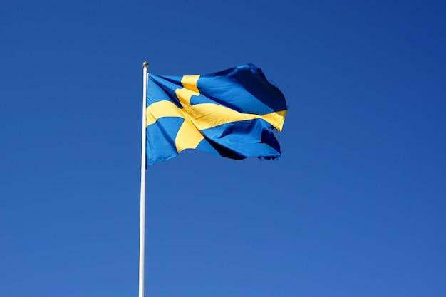 Швеция флаг развевается на фоне голубого неба