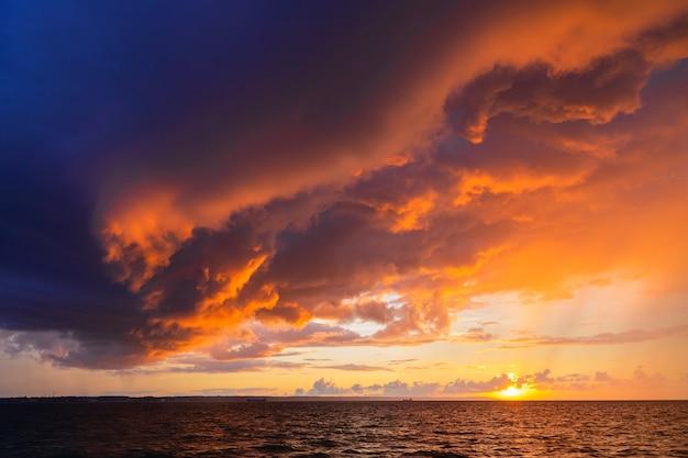 海の上の曇りの暗い空を通して劇的な夕日。