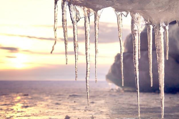 美しいつららは日没に対して太陽の下で輝きます。バイカル湖の冬時間