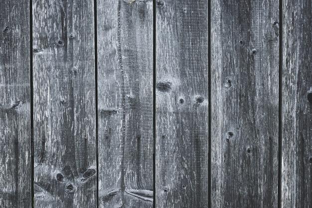Темно-серый деревянный забор. потертые доски с гвоздями.
