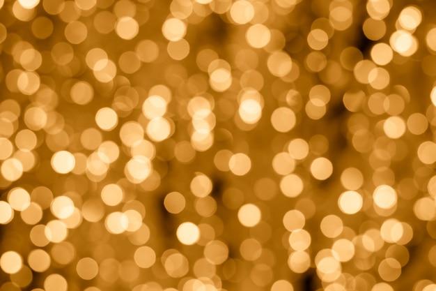 Абстрактный золотой фон с огнями боке. световой фон. размытый эффект.