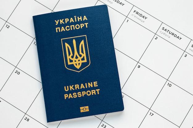 Украинский биометрический паспорт на белой странице календаря. планирование отпуска концепции. международный синий паспорт.
